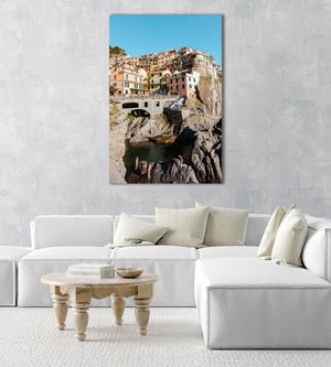 People swimming amongst bridge and colorful buildings of Manarola in Cinque Terre in an acrylic/perspex frame