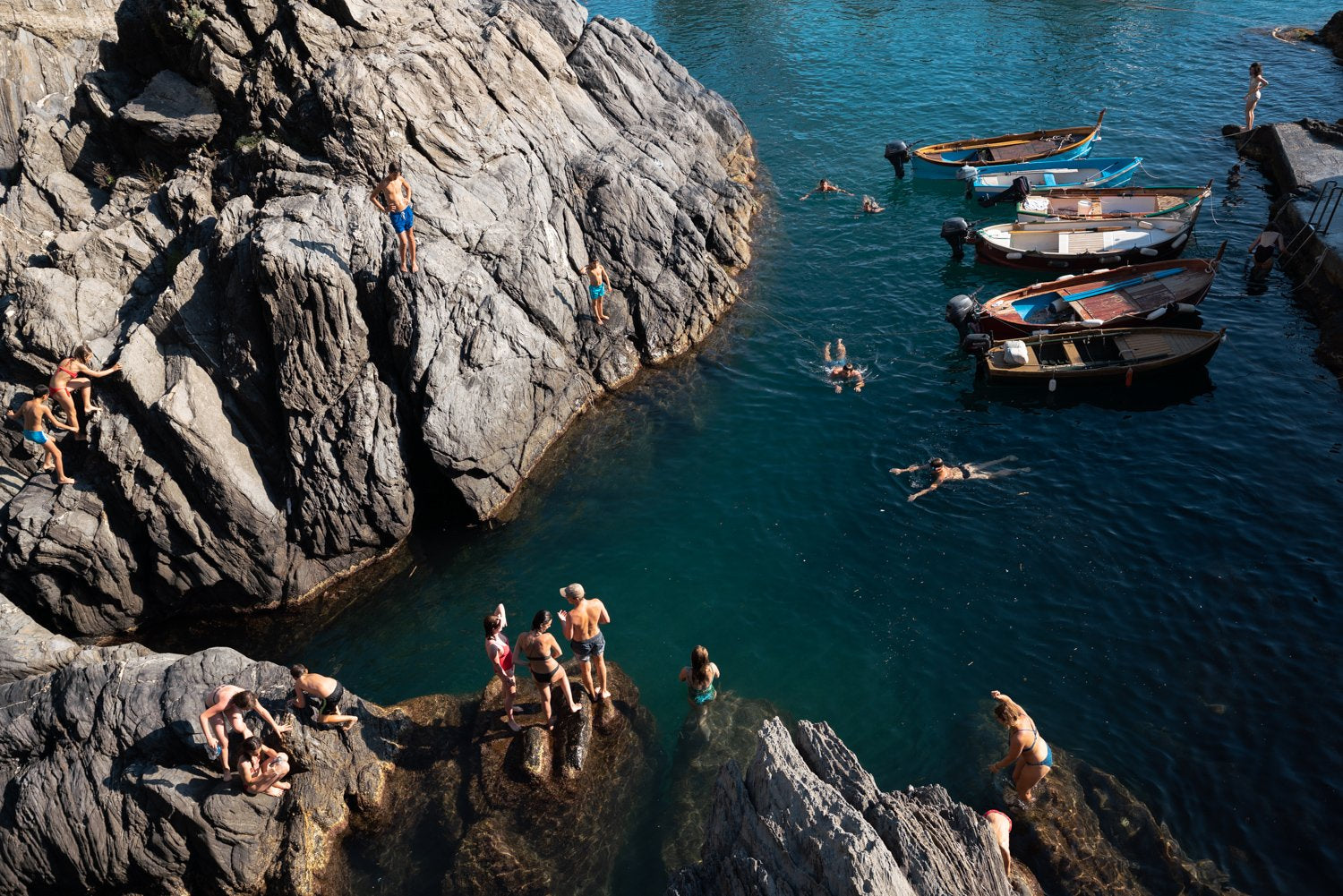 People swimming along dark rocks in Manarola Cinque Terre