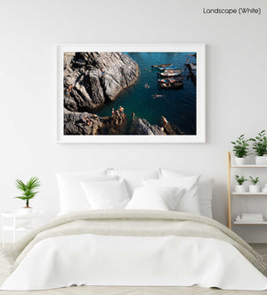 People swimming along dark rocks in Manarola Cinque Terre in a white fine art frame