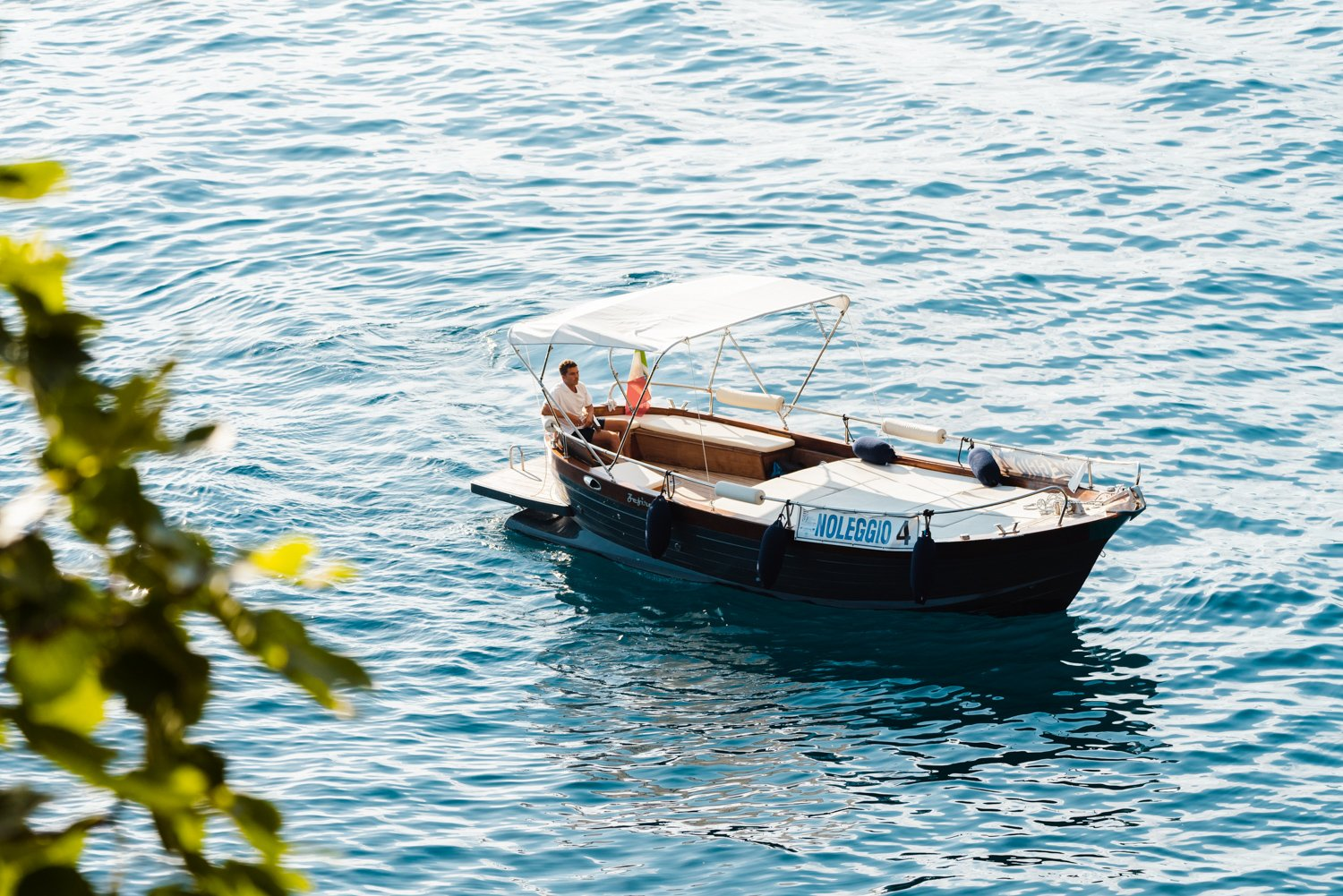 Man driving a rental boat along Cinque Terre coastline