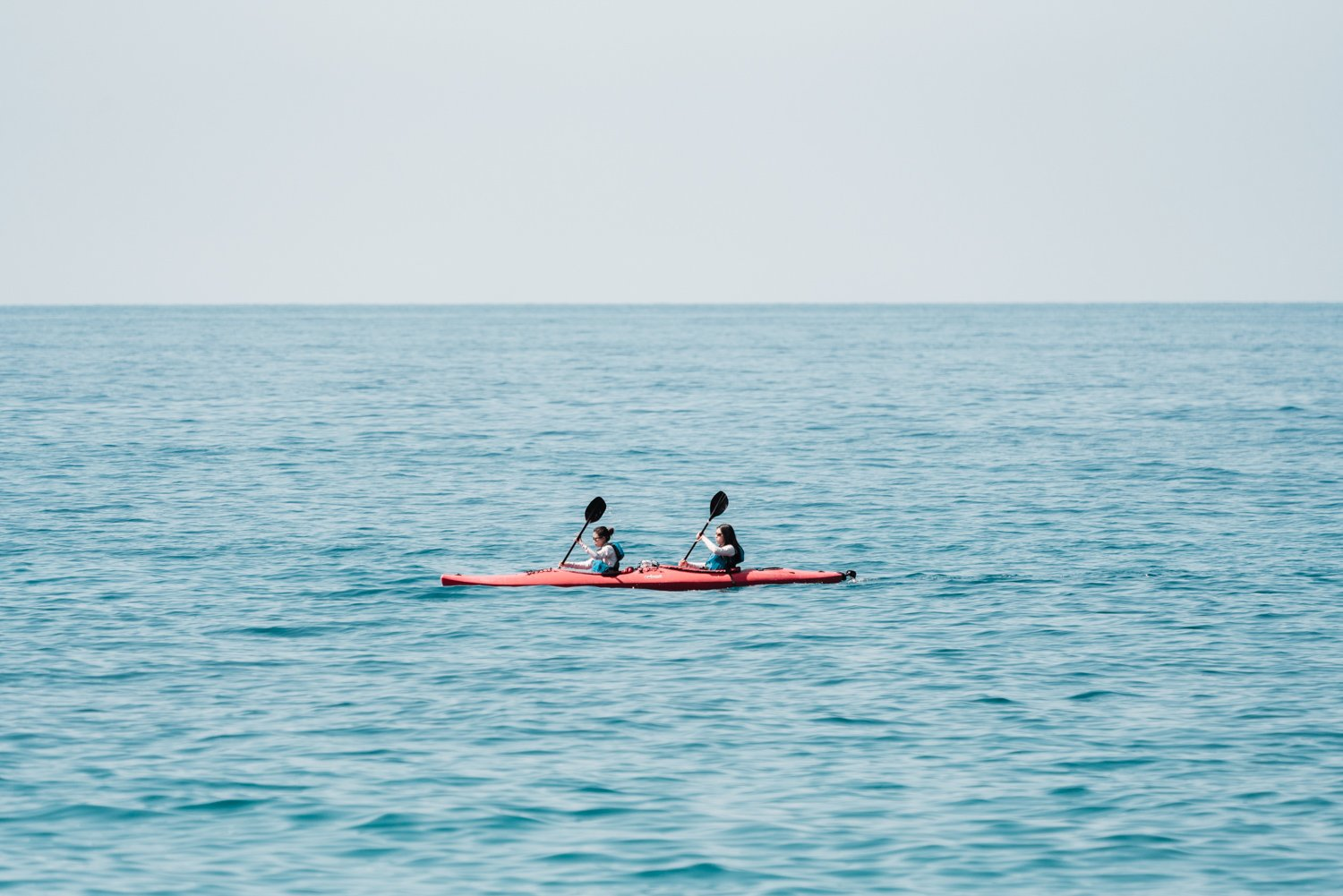 Two women paddling a red kayak in Cinque Terre