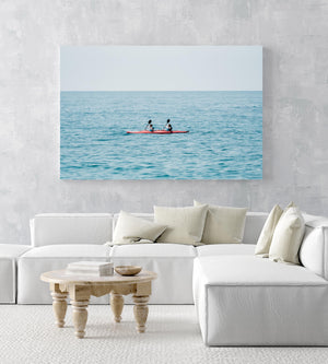 Two women paddling a red kayak in Cinque Terre in an acrylic/perspex frame