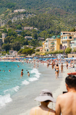 People walking and swimming in blue water of Monterosso beach in Cinque Terre