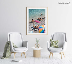 Colorful umbrella, pink lilo and people sitting along blue ocean water in a natural fine art frame