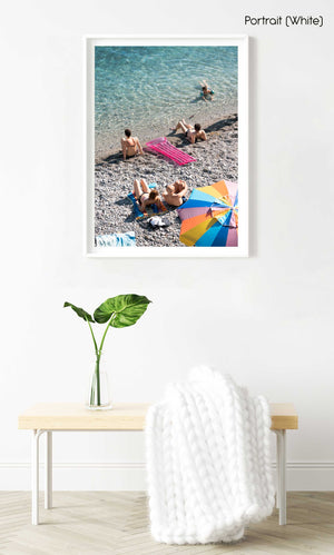 Colorful umbrella, pink lilo and people sitting along blue ocean water in a white fine art frame