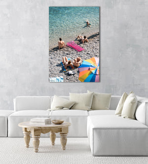 Colorful umbrella, pink lilo and people sitting along blue ocean water in an acrylic/perspex frame