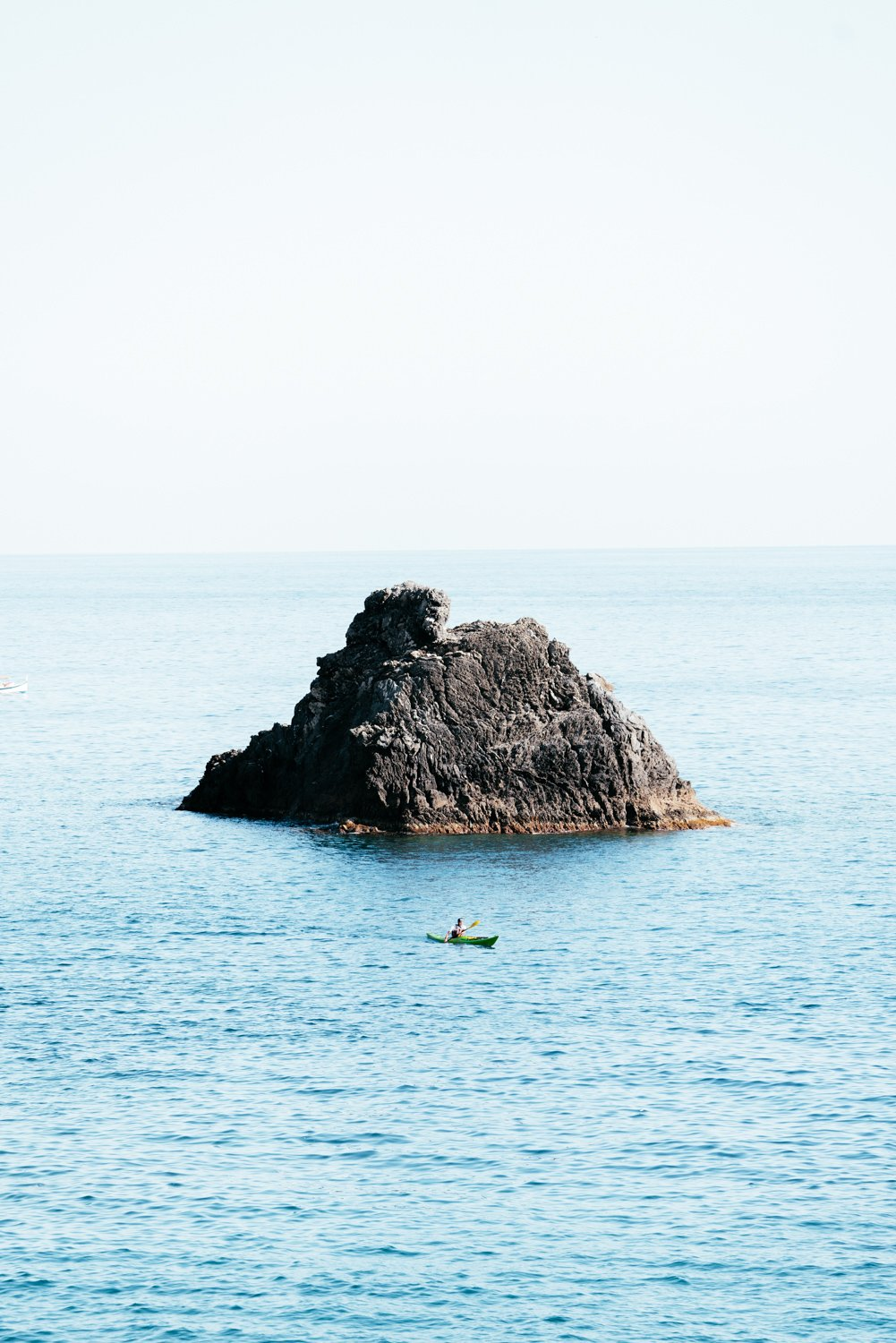 Man paddling in kayak at big rock in blue ocean in Cinque Terre