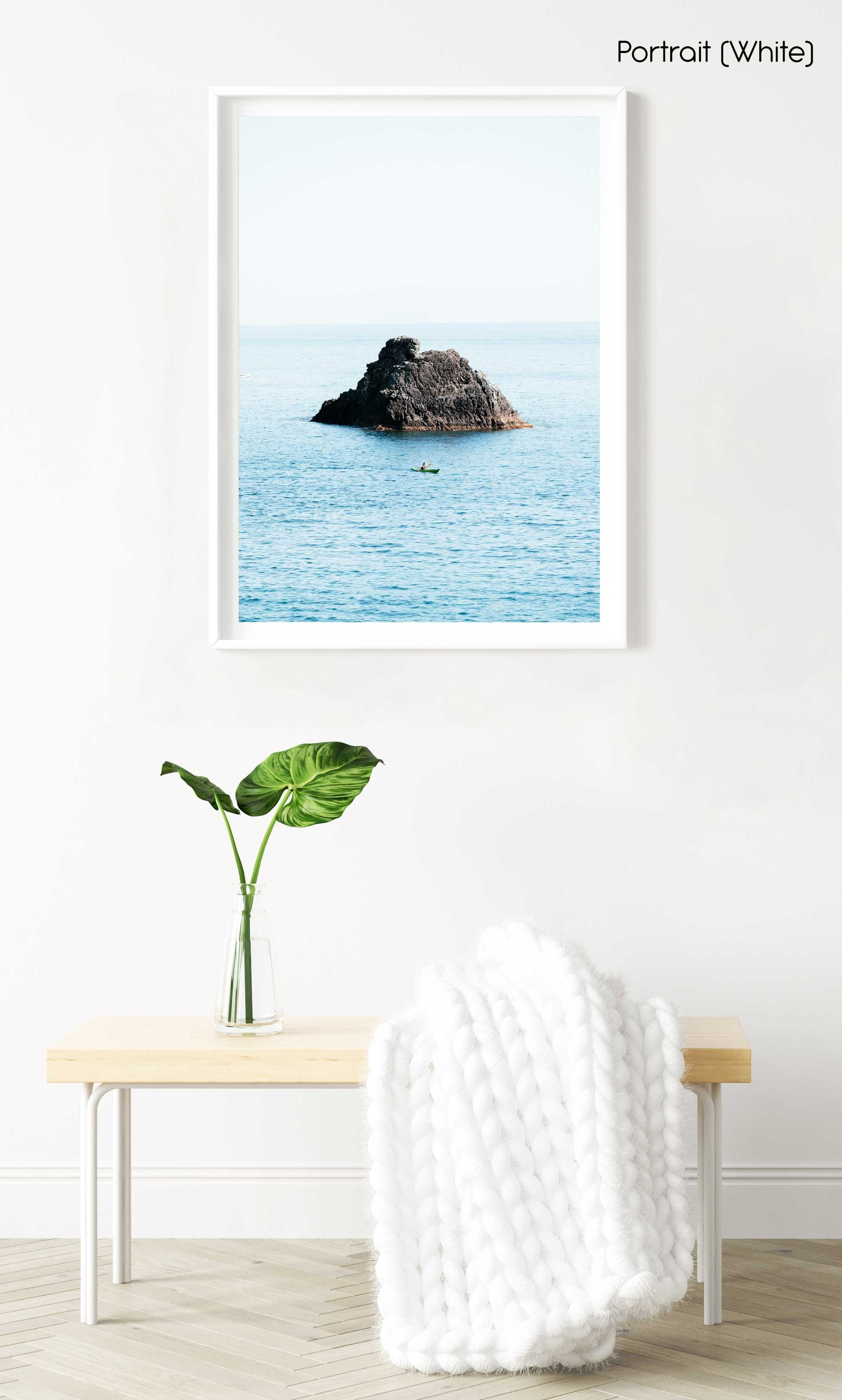 Man paddling in kayak at big rock in blue ocean in Cinque Terre in a white fine art frame