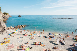 Lots of people lying on old town Monterosso beach in Italy