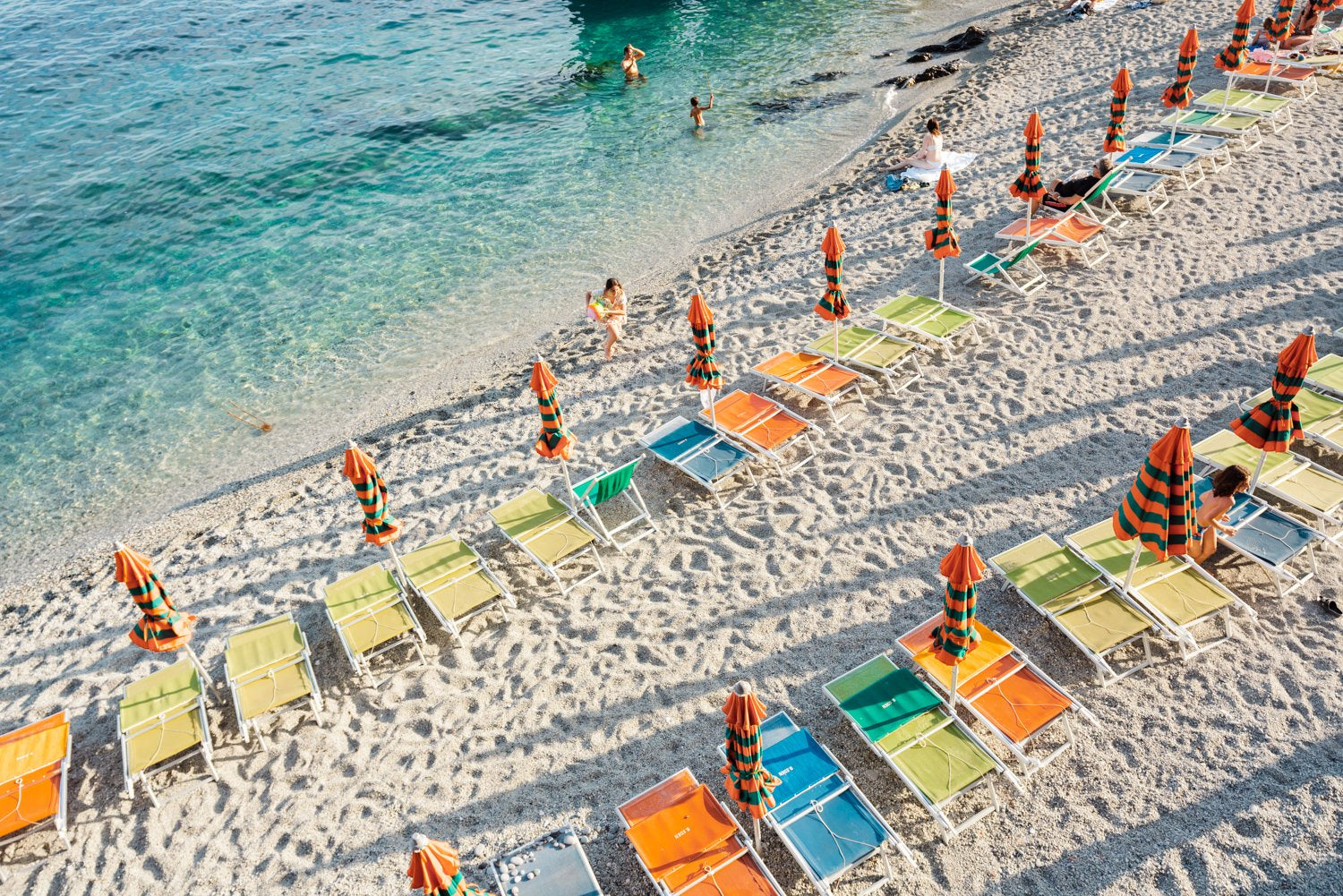 Orange, green and blue chairs on beach in Cinque Terre
