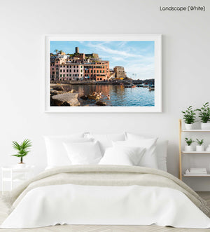 People swimming at Vernazza beach near buildings in a white fine art frame
