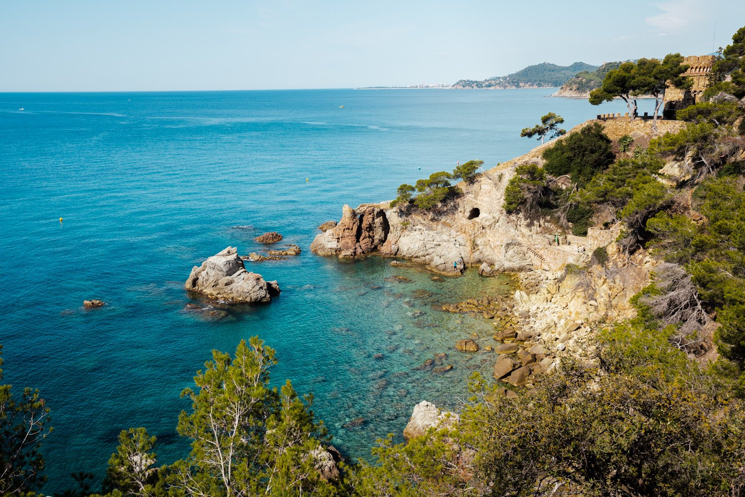 Green trees and bright blue water along Costa Brava coast