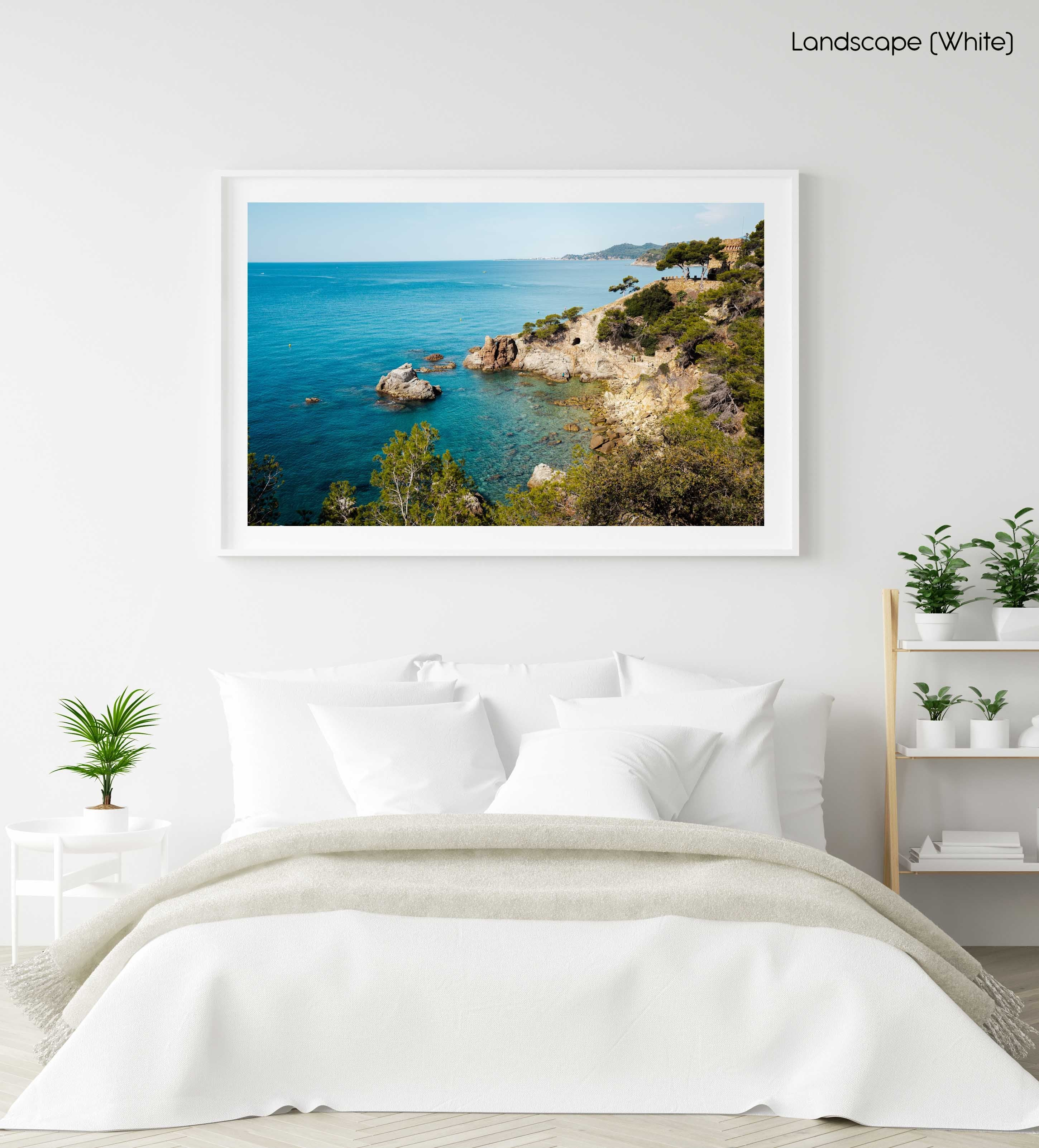Green trees and bright blue water along Costa Brava coast in a white fine art frame