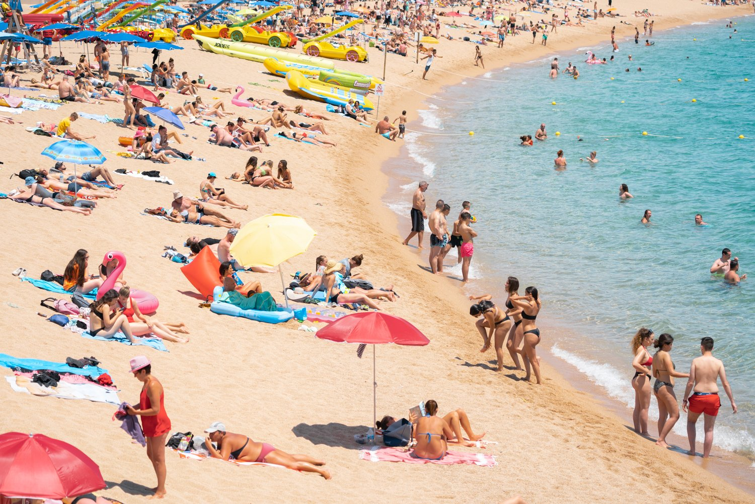 Colors of umbrellas, sand and people on Lloret de Mar beach