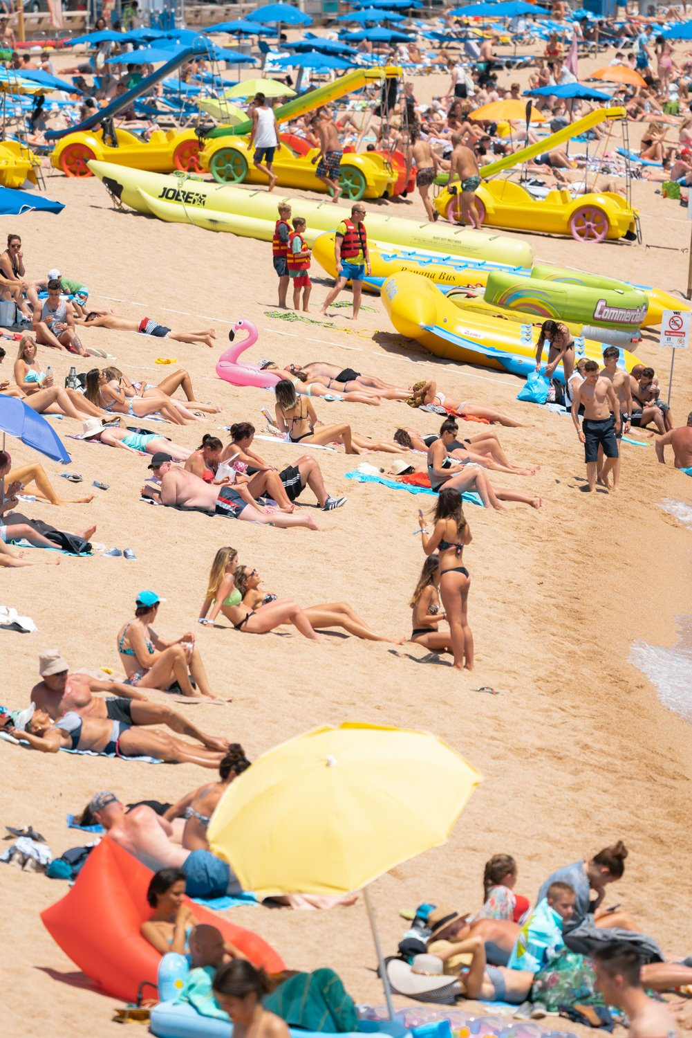 People lying on beach in Costa Brava