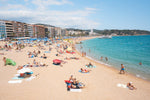 Crowded beach of Lloret de Mar with blue water in summer