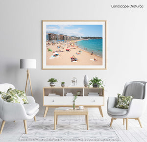 Crowded beach of Lloret de Mar with blue water in summer in a natural fine art frame