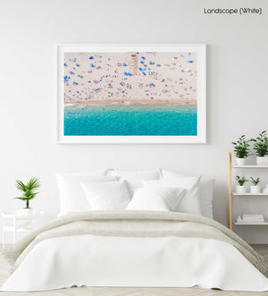 Aerial of blue ocean and people lying on Lloret de Mar beach in a white fine art frame