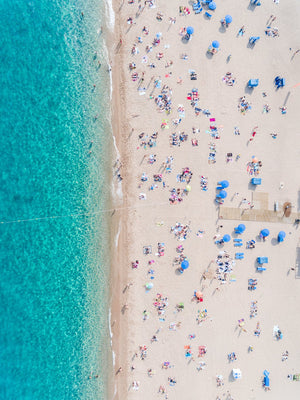 Aerial of blue ocean and people lying on Lloret de Mar beach