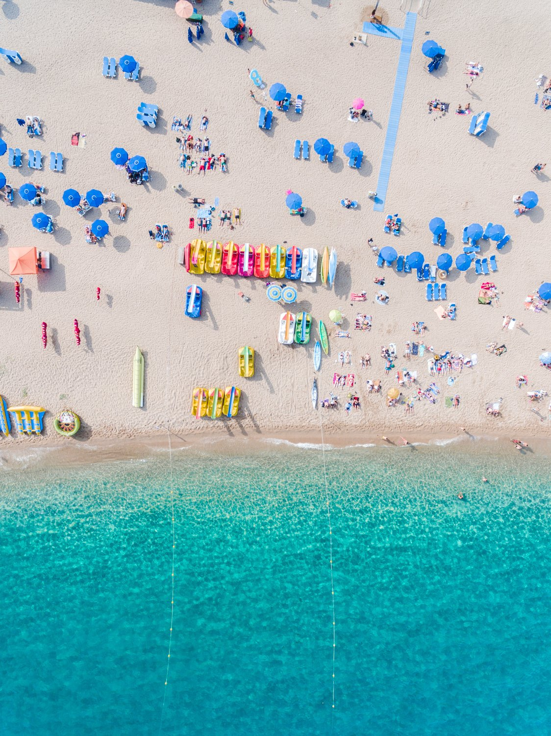 Colorful umbrellas, boats and water seen from air above Lloret de Mar beach