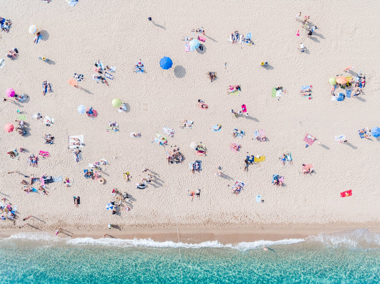 People, umbrellas and towels seen from above