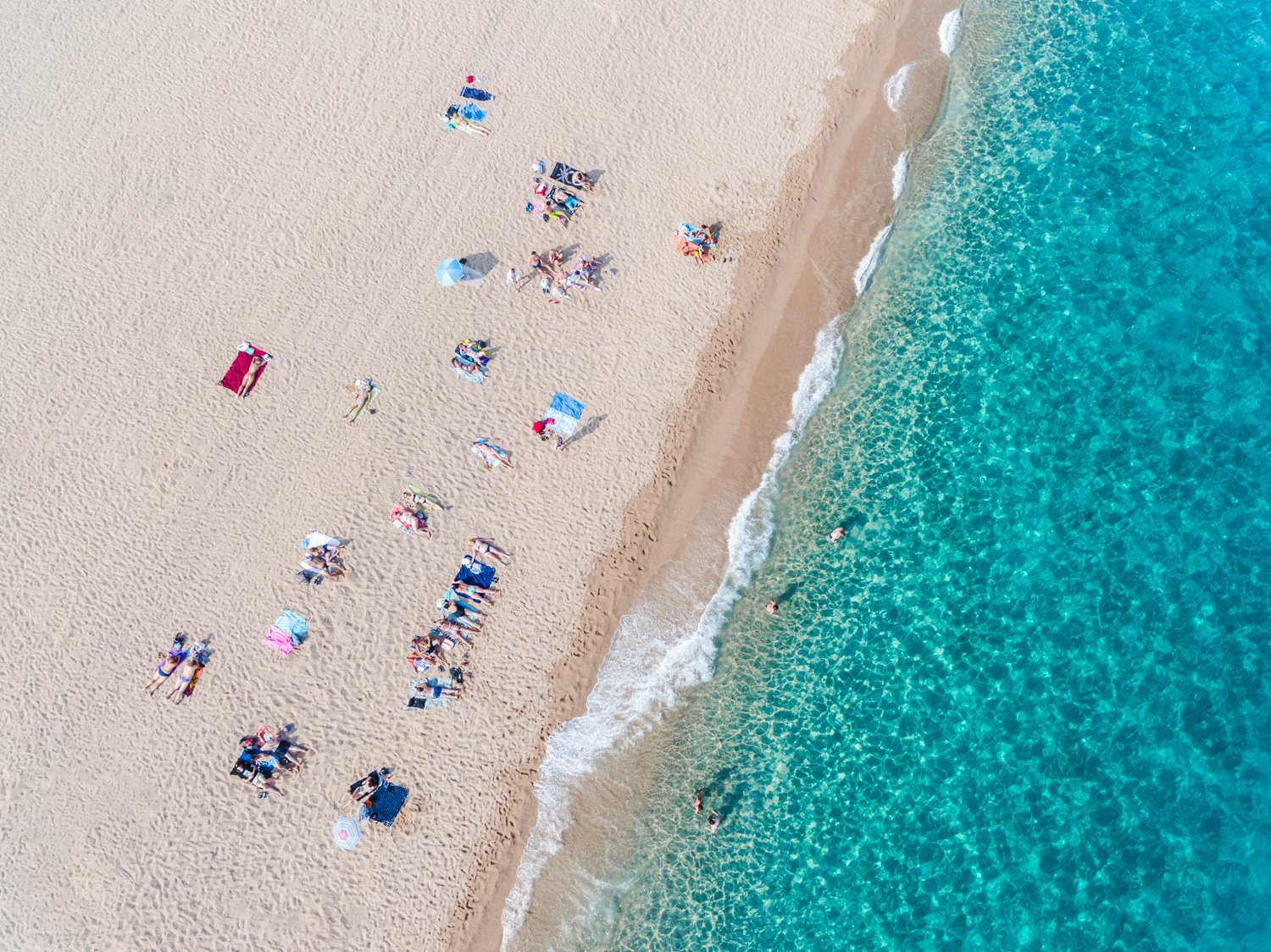 Simplistic aerial of blue ocean and people sunbathing in Costa Brava