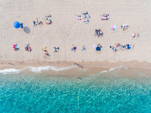 Lines of people tanning on beach in Spain from aerial view