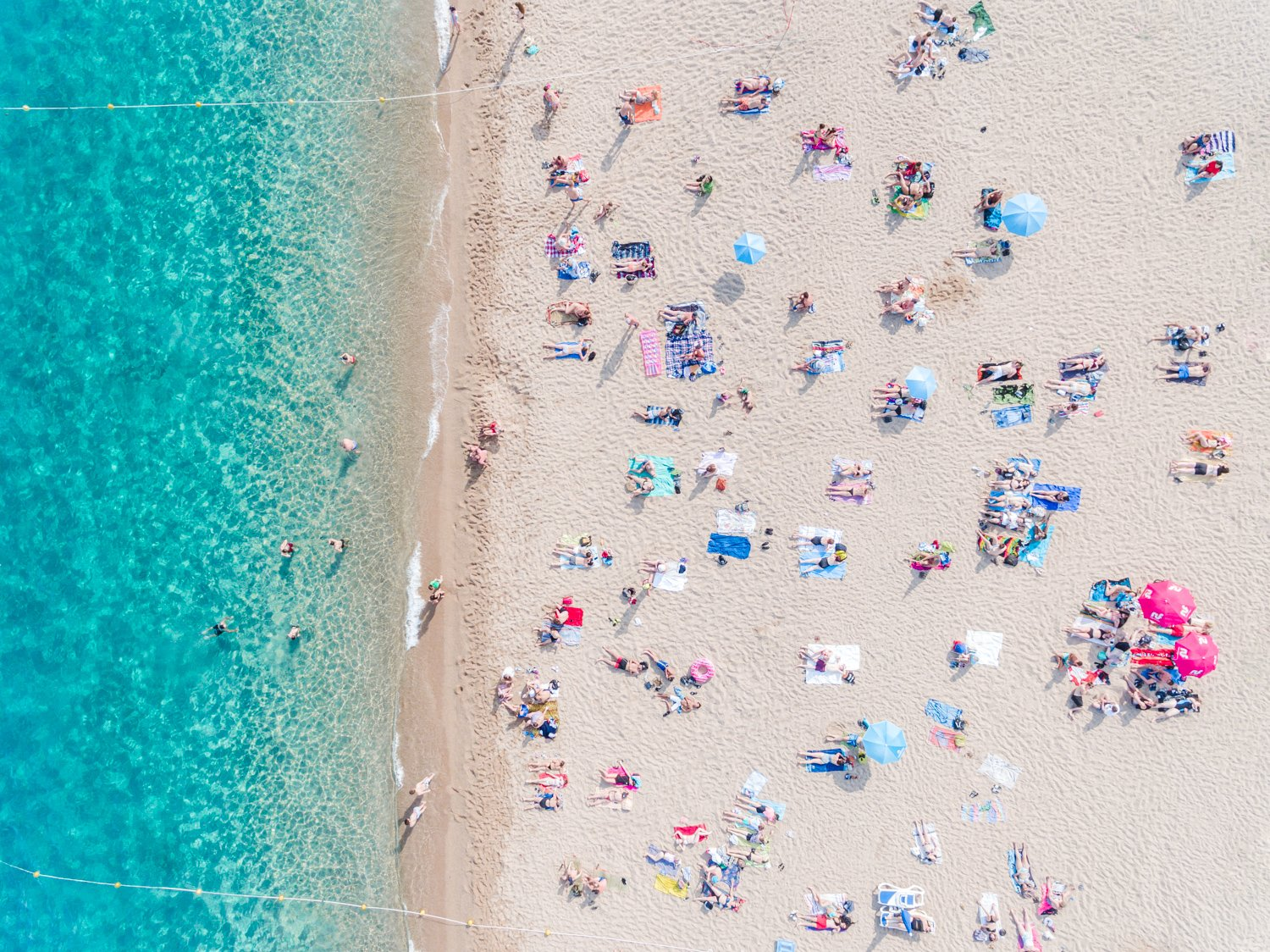 Topdown view of people lying on beach with bright blue water in Costa Brava