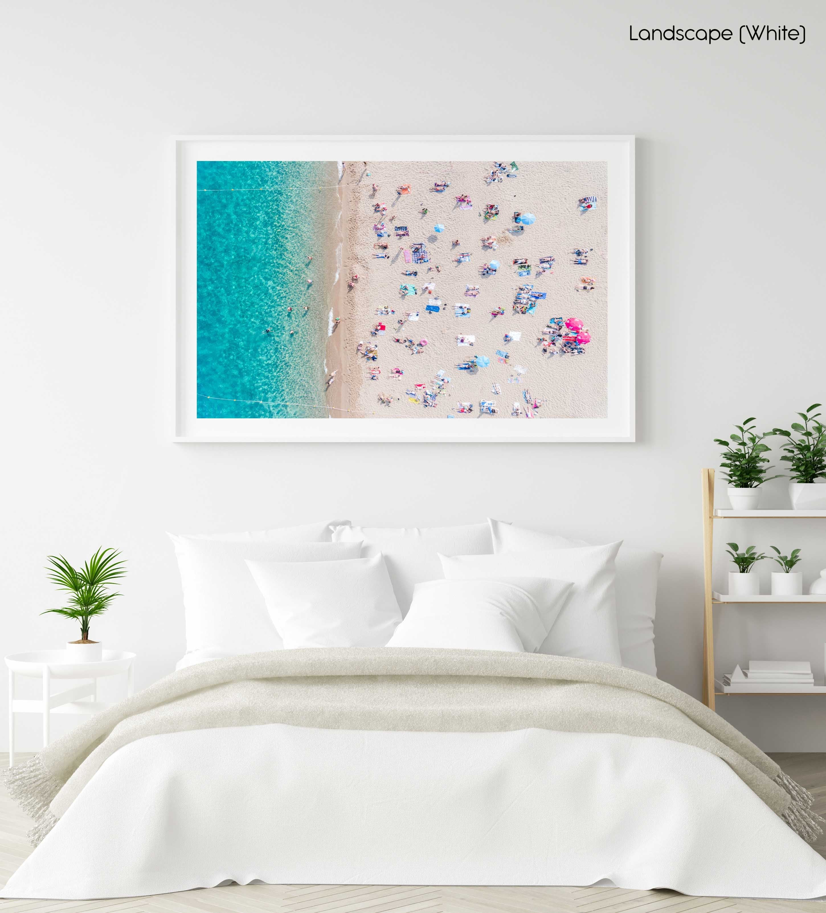 Topdown view of people lying on beach with bright blue water in Costa Brava in a white fine art frame