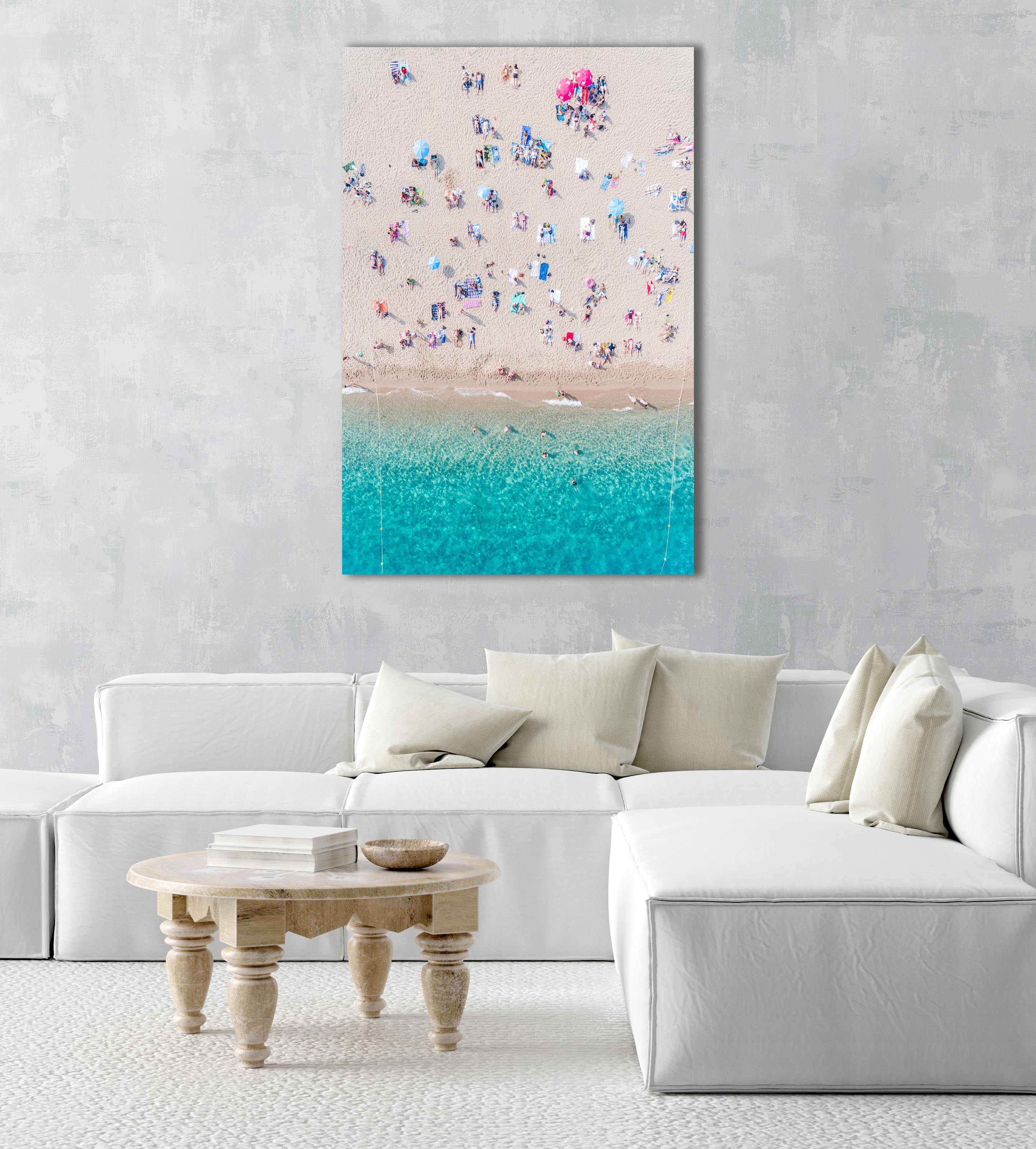 Topdown view of people lying on beach with bright blue water in Costa Brava in a natural fine art frame