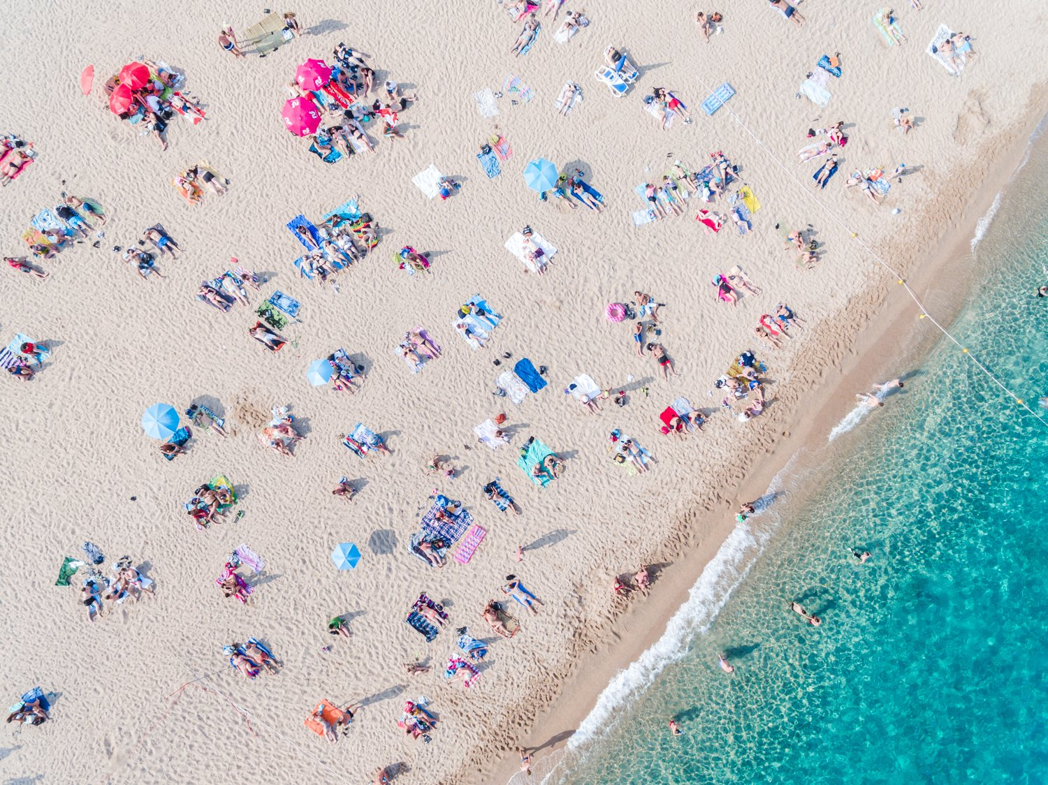 Aerial of people lying in the sun on the beach