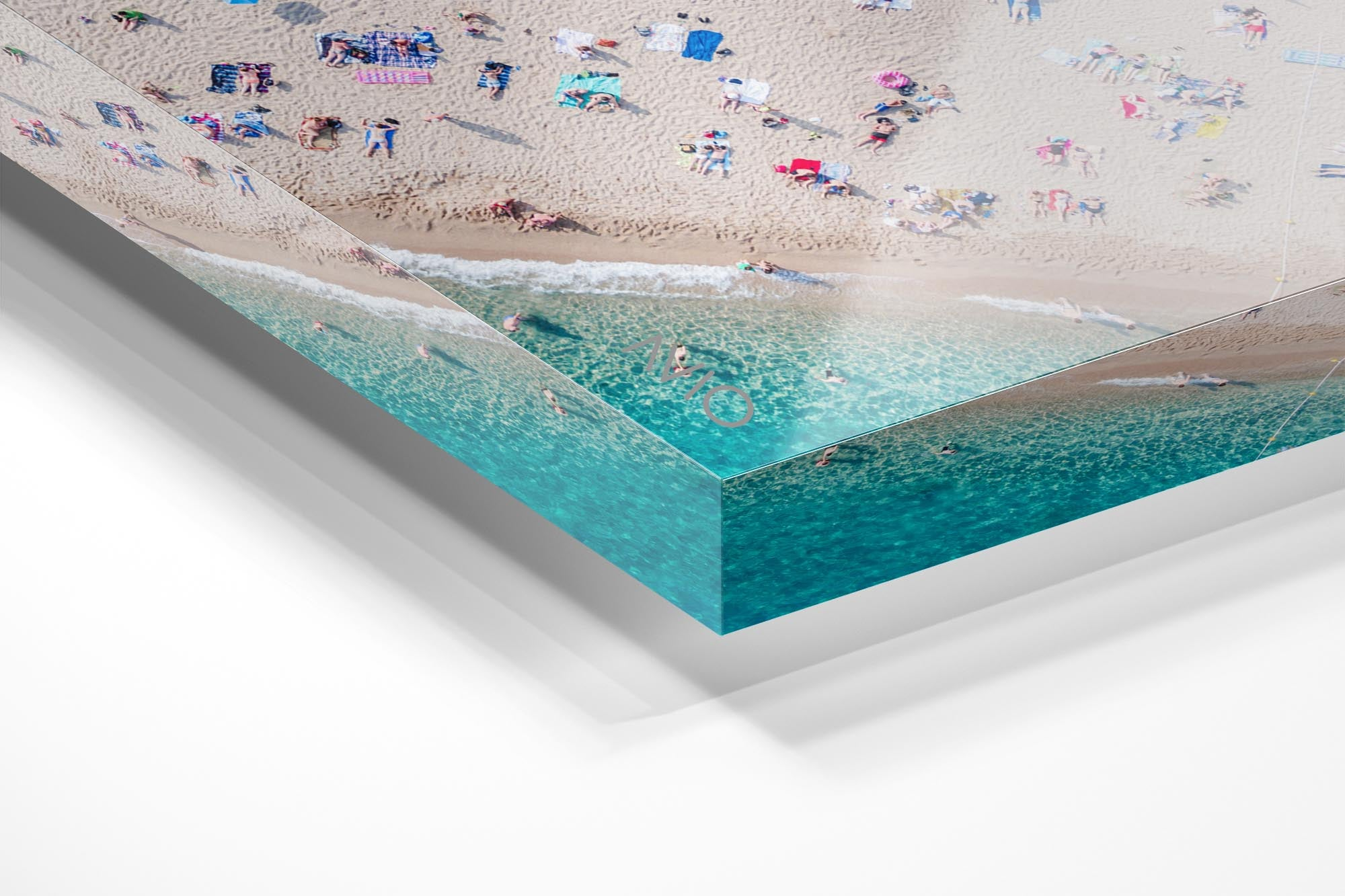 Aerial of people lying in the sun on the beach in an acrylic/perspex frame