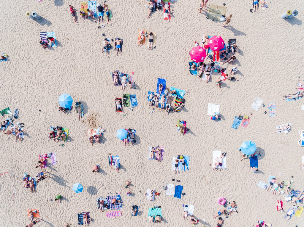 Topdown view of people lying on sand, colorful umbrellas and towels in Costa Brava