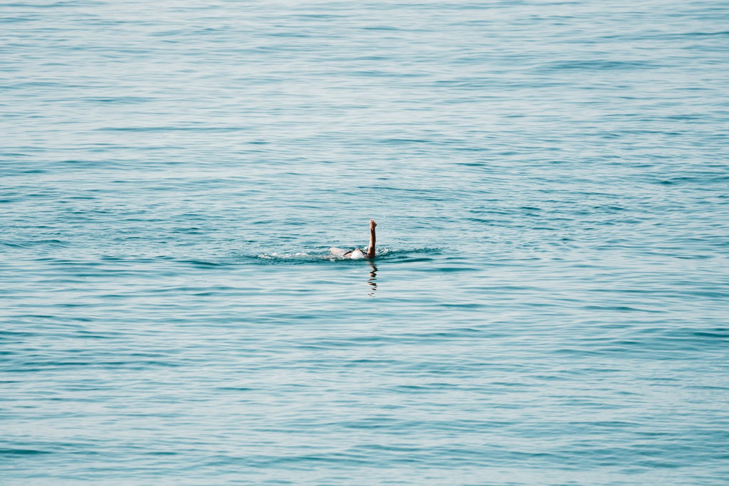 Woman swimming backstroke in the ocean in Costa Brava