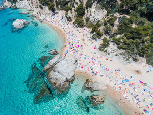 Aerial of bright blue sea, colorful umbrellas and people at Cala sa Boadella beach