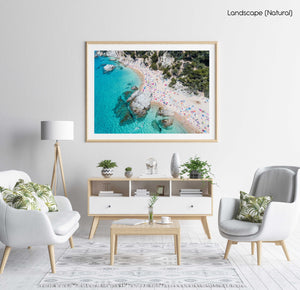 Aerial of bright blue sea, colorful umbrellas and people at Cala sa Boadella beach in a natural fine art frame