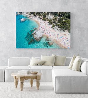 Aerial of bright blue sea, colorful umbrellas and people at Cala sa Boadella beach in an acrylic/perspex frame