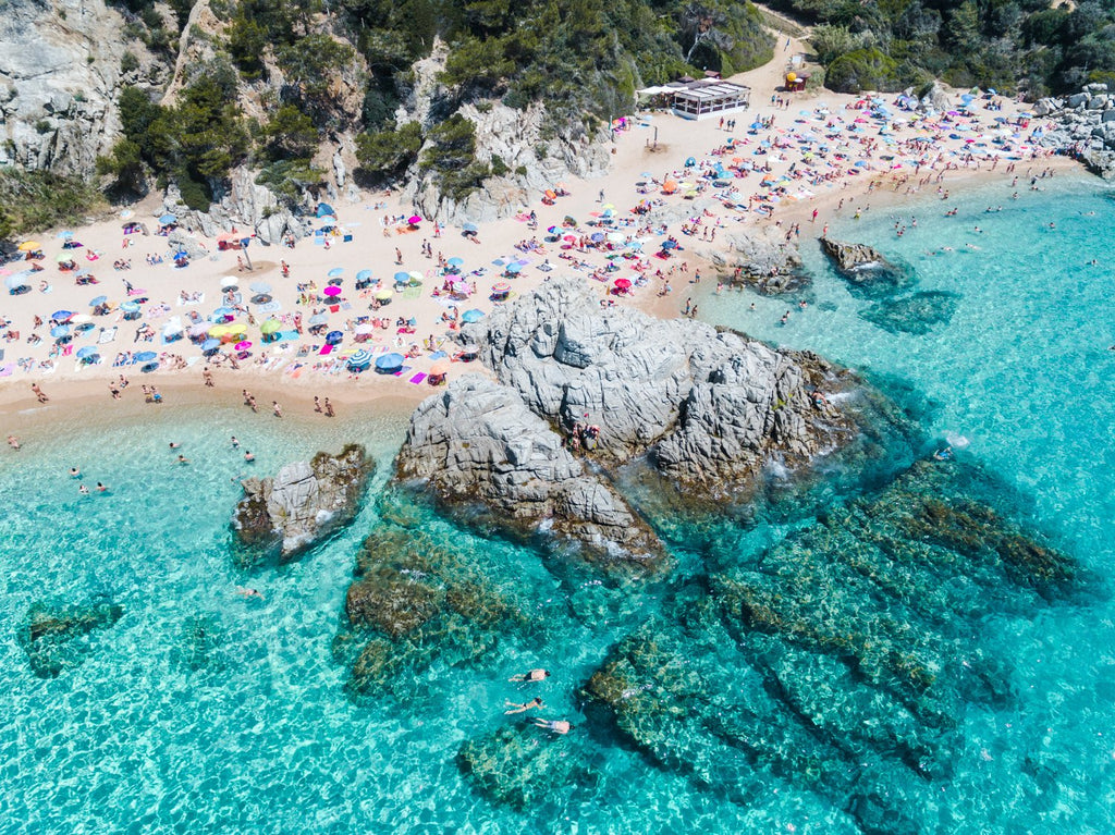 People swimming, snorkeling and tanning along blue water of spanish beach