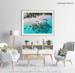 People swimming, snorkeling and tanning along blue water of spanish beach in a natural fine art frame