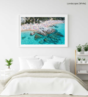 People swimming, snorkeling and tanning along blue water of spanish beach in a white fine art frame
