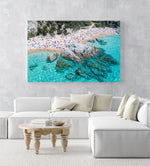People swimming, snorkeling and tanning along blue water of spanish beach in an acrylic/perspex frame