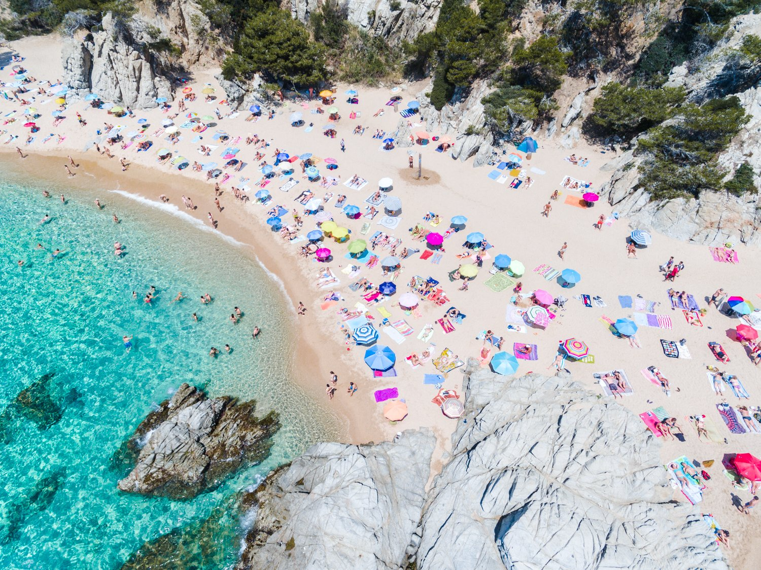Colorful umbrellas and people lying on beach taken from the sky