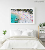 Colorful umbrellas and people lying on beach taken from the sky in a white fine art frame