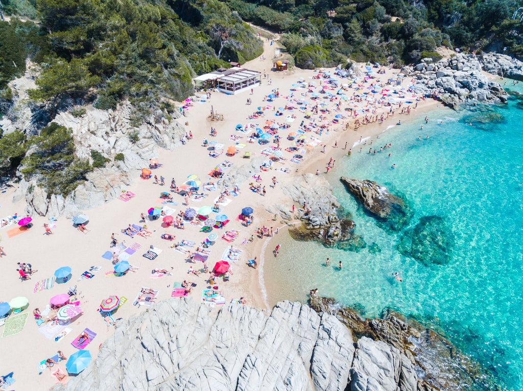 Busy beach full of people and umbrellas in Costa Brava