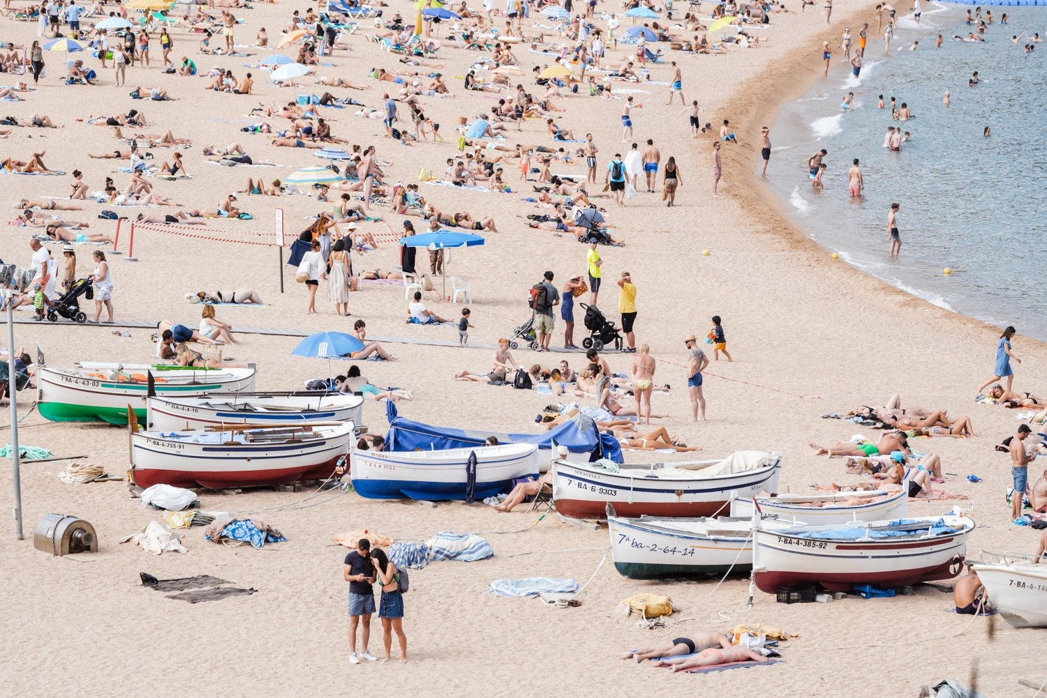Boats and people beached along Tossa de Mar beach