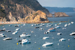 Many boats anchored off in ocean along Tossa de Mar beach in Spain