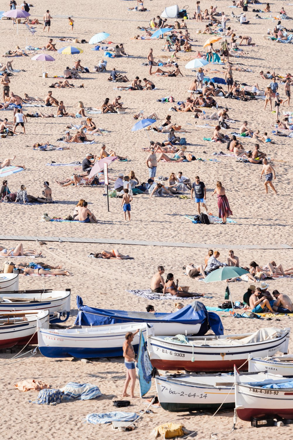 Boats and people scattered on Tossa de Mar beach