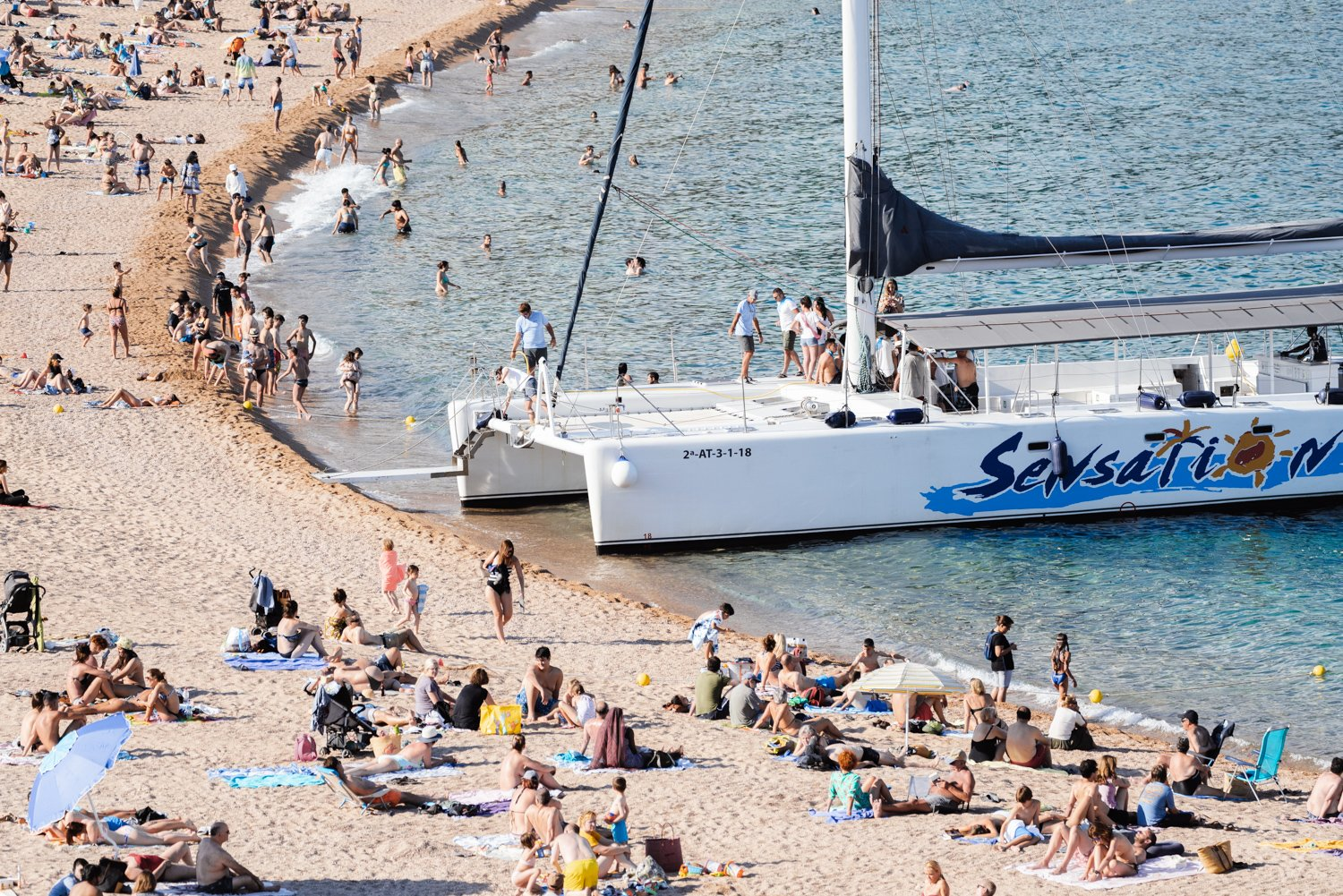 Sailing boat parked on a crowded beach in Spain