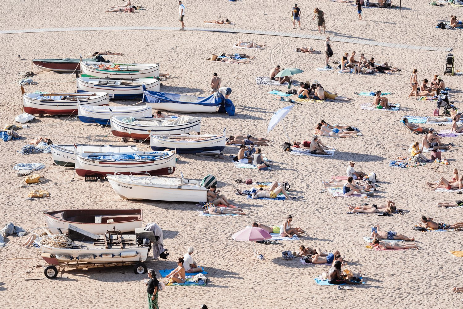People and boats lying on the sand of Costa Brava