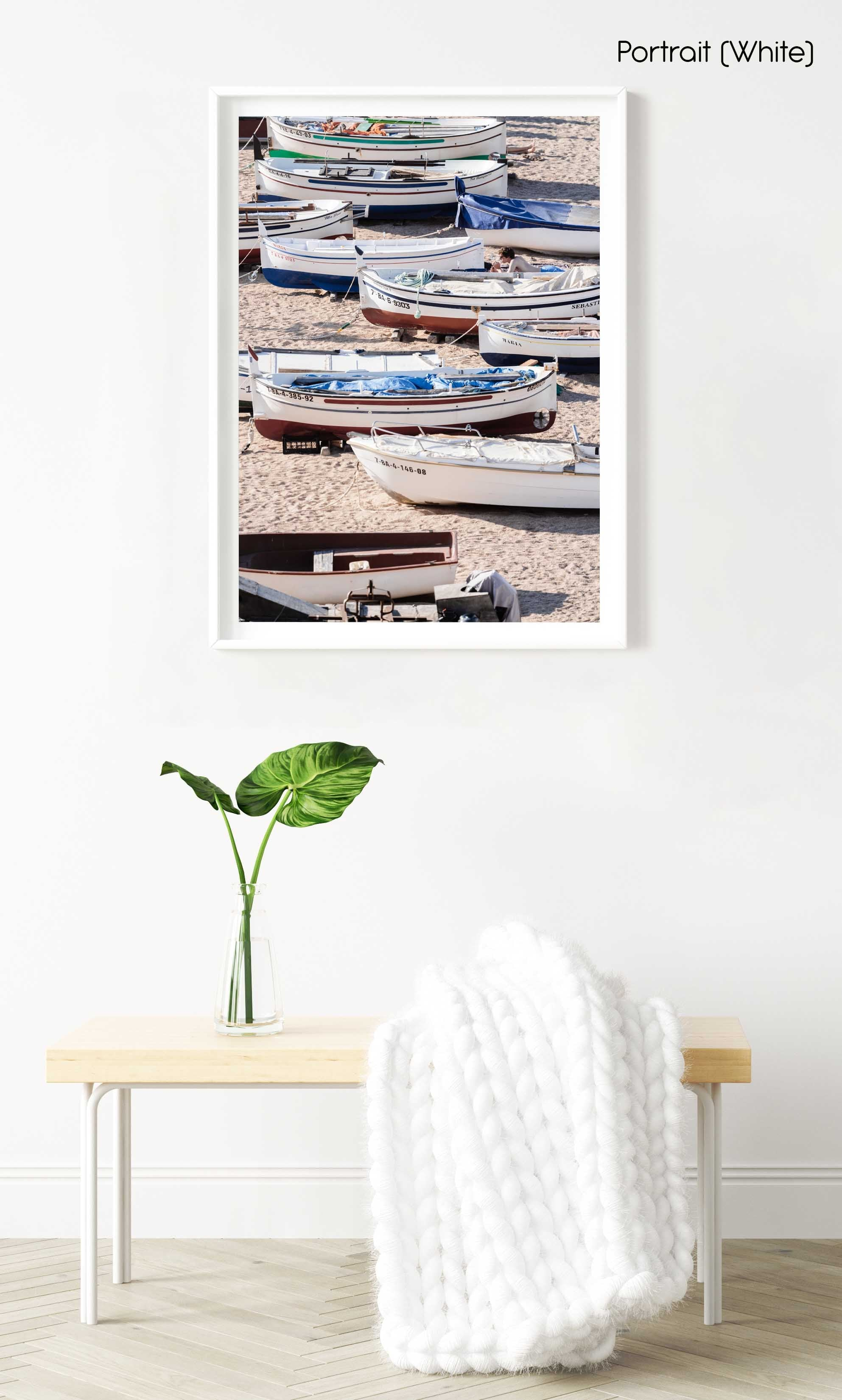 Empty boats beached on the sand in a white fine art frame
